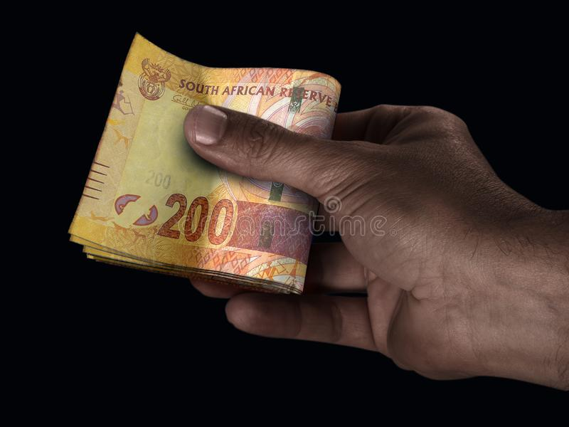 Black Hand And Rand Cash. A black male hand handing over a wad of folded South Africa Rand bank notes on an isolated background stock photos