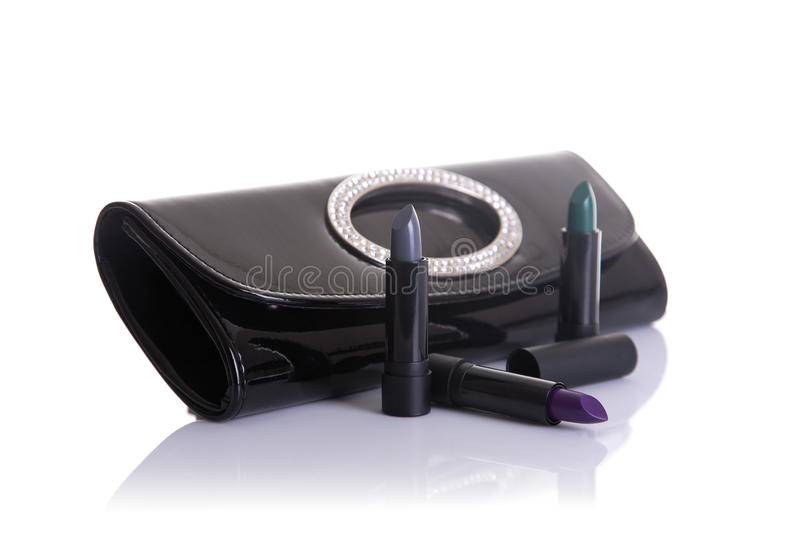 Black handbag clutch and lipsticks in green, gray and purple col. Ors, isolated on white background with natural reflection stock photography