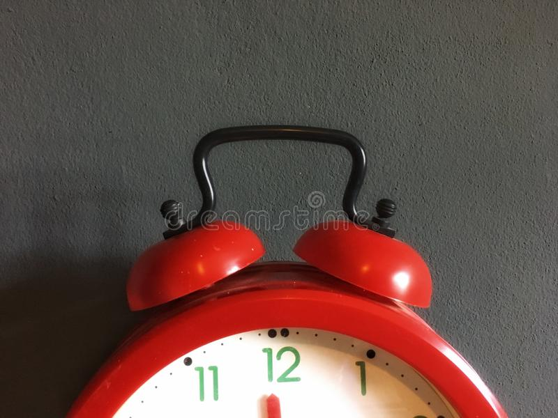 Black handle on red clock with vintage design. Black handle on red clock with vintage design in front of gray background stock photos