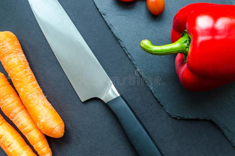 Black Handled Gray Kitchen Knife Beside Orange Carrots and Red Bellpepper royalty free stock photos