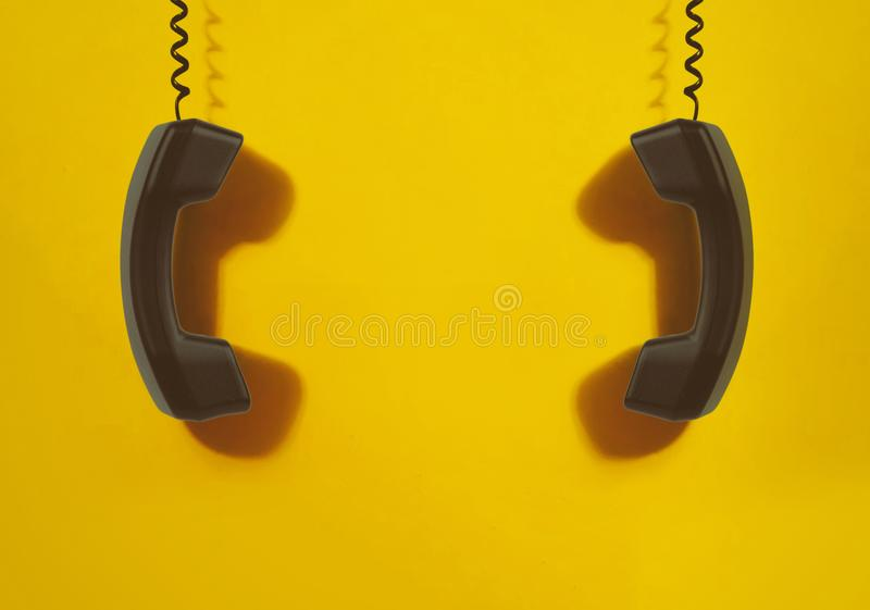 Black handsets on yellow background. Networking, Social Media and Internet Concept royalty free stock photo