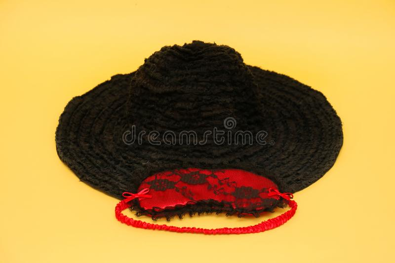 Black hat with mask. Retro black textile hat with red sexy eye mask on yellow background stock images