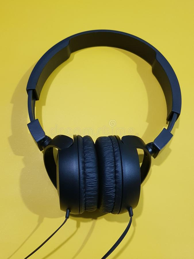 Black headphone. On yellow background stock image