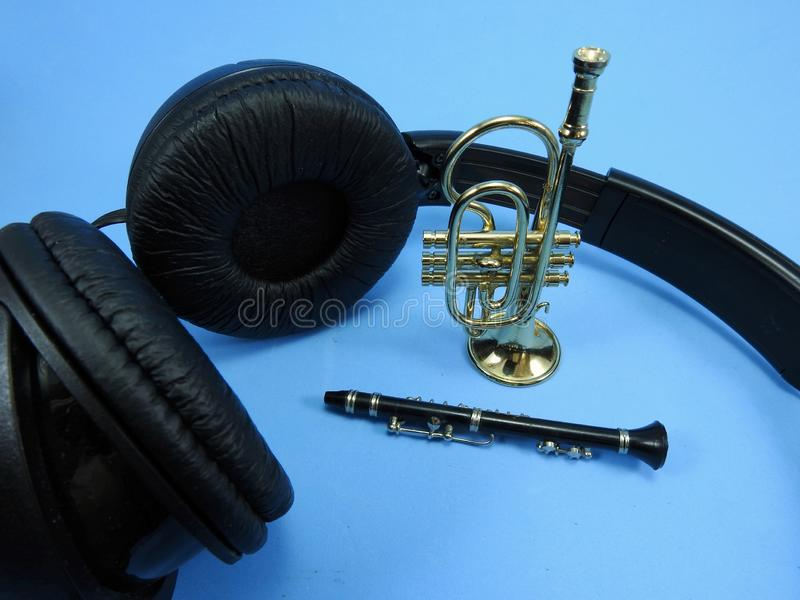 Black headphones, a clarinet and a trumpet. The musical instruments are miniatures. royalty free stock image