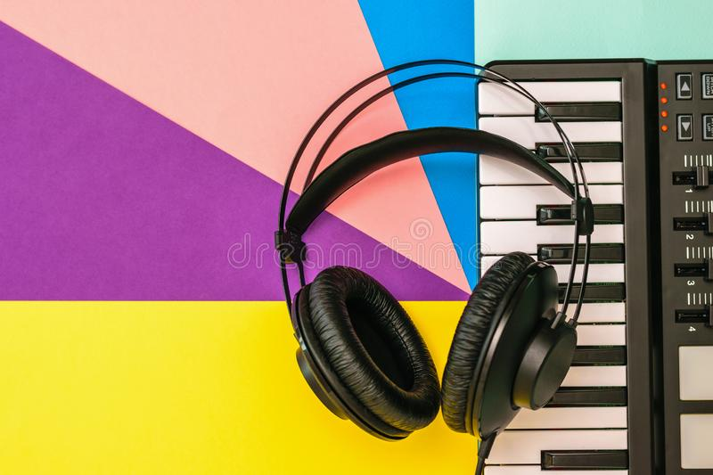 Black headphones and a music mixer on a multicolored background. The view from the top. Black headphones and a music mixer on a multicolored background royalty free stock images