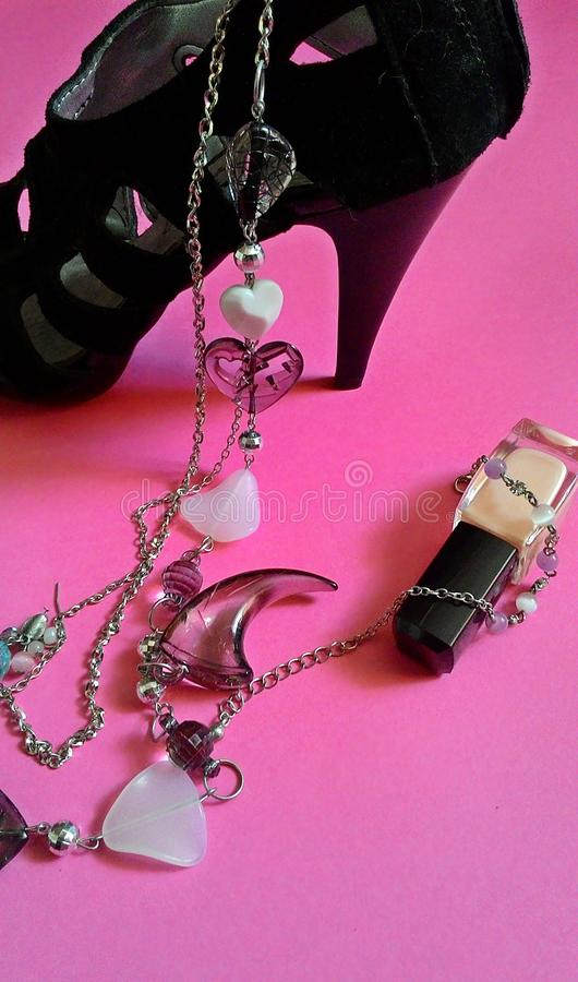 Black heel and jewelry. Black heel, necklace and nail polish on pink background royalty free stock photo