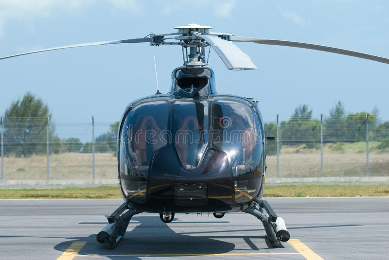 Black helicopter. Front view of black helicopter at an airport stock images