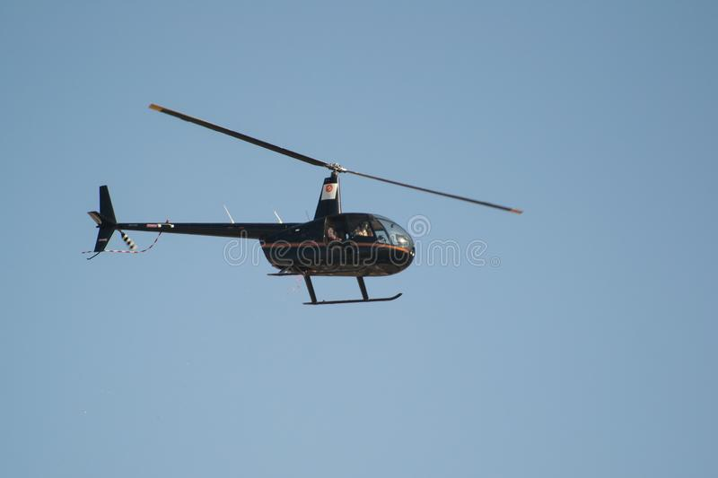 Black Helicopter in Sky. Black Helicopter or Chopper flying in Blue Sky isolated stock photos