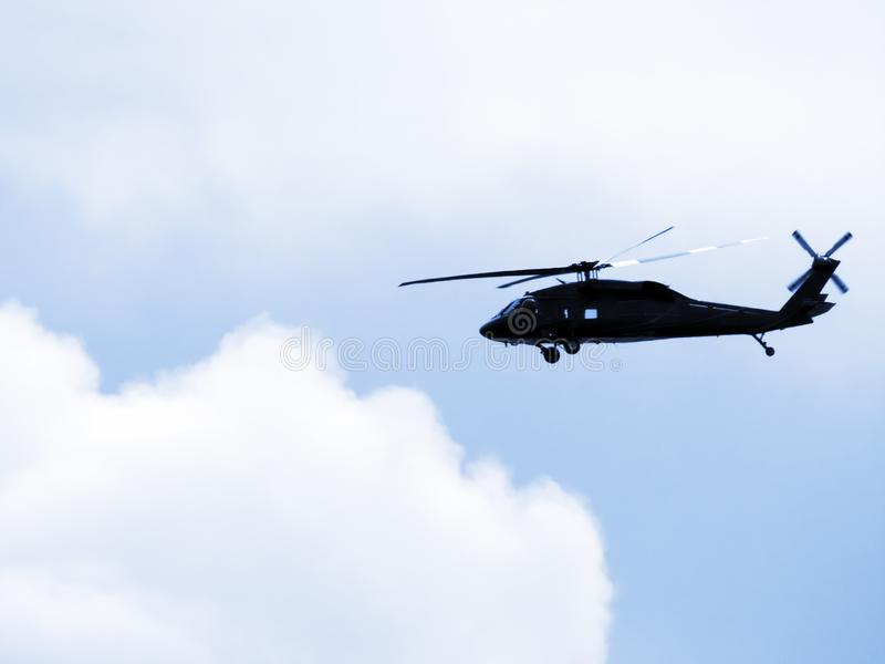Black helicopter in clouds. Black helicopter in a blue sky with puffy white clouds stock photos