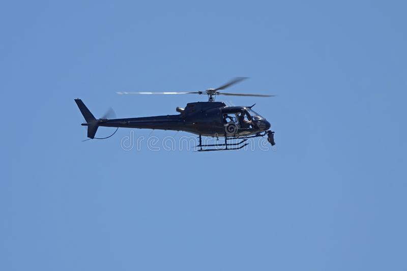 Black Helicopter Filming and Hovering from Side View. An unmarked black helicopter is shown from a side view while filming below, set against a solid, blue sky royalty free stock image