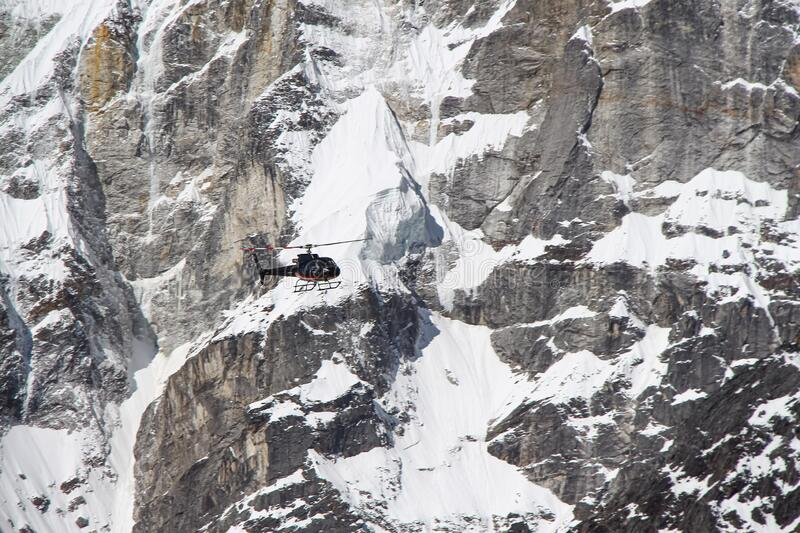 Black helicopter flies in Himalayas. Unrecognisable black helicopter flies in Himalayas with blurred mountains in the background. Ice and snow covers the stock image