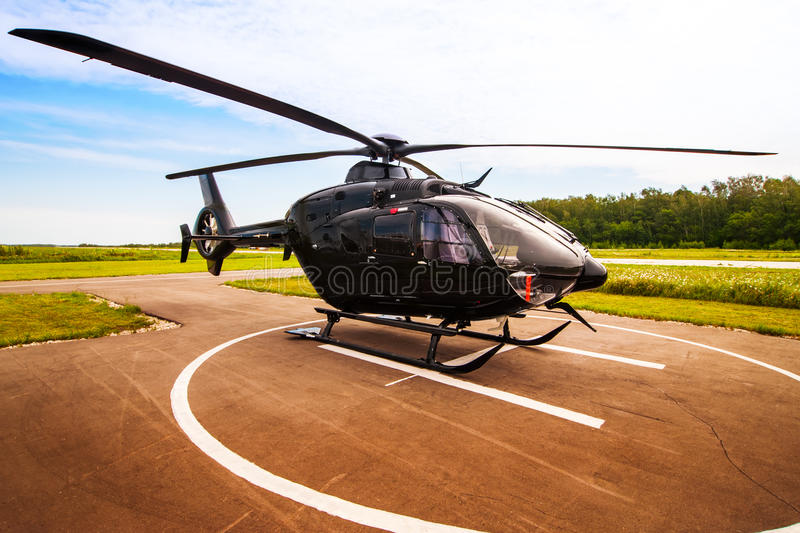 Black helicopter. On the helipad royalty free stock images