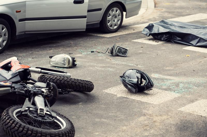 Black helmet and motorcycle on the road after fatal collision wi royalty free stock photo