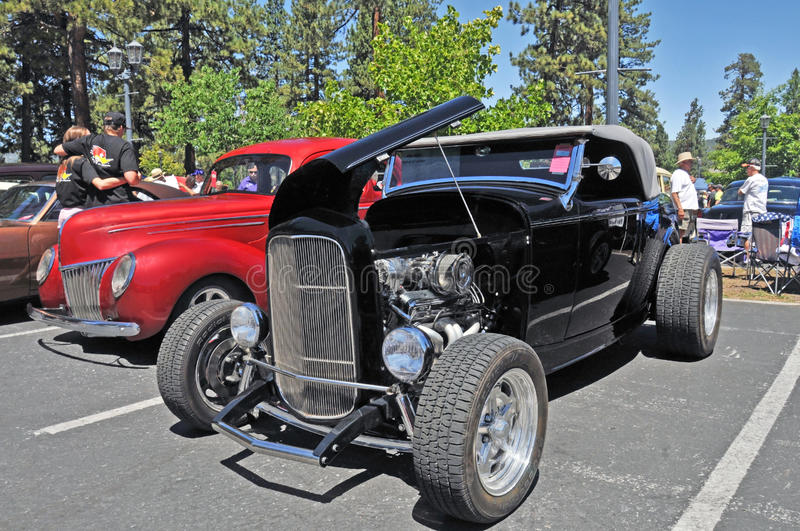 Black High Boy Roadster. This high boy roadster has some nice touches with a high performance V-8 engine, alloy spoke wheels, and a gray soft top. Tooling down stock photography