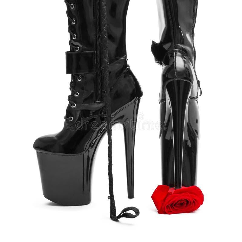 Black high heel platform boots tramp rose. Bdsm stock photo