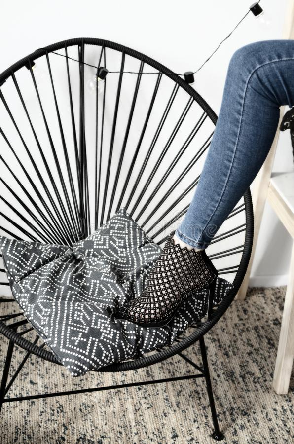 Black high-heeled shoes elegant leather women`s shoes on the rattan chair, geometry, light glossy heel shoes. Black high-heeled shoes elegant leather women`s royalty free stock image