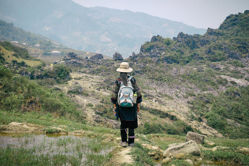 Black Hmong woman on rice terraces in SaPa. Sapa, Vietnam - April 14, 2016: Black Hmong minority woman in traditional clothes on rice terraces landscape in Sa Pa royalty free stock photo