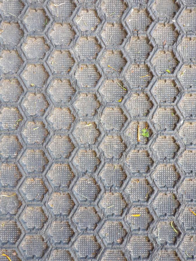 Black honeycomb pattern floor matt. Close up with some grass in the rifles stock images