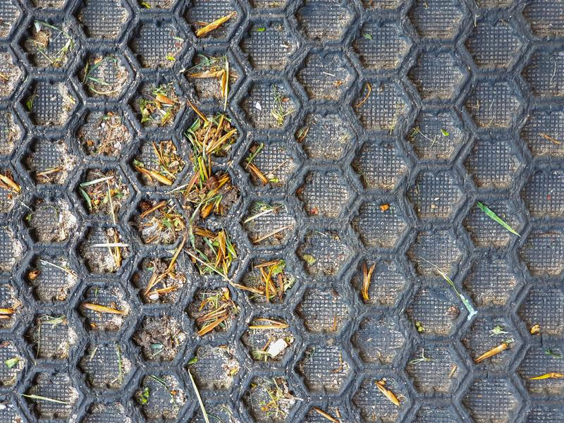 Black honeycomb pattern floor matt. Close up with some grass in the rifles royalty free stock photography