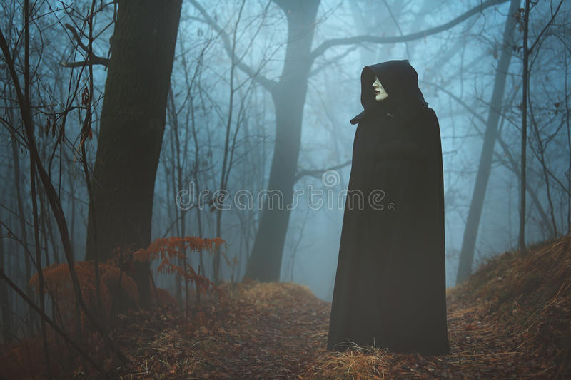 Black hooded person in the fog stock photo