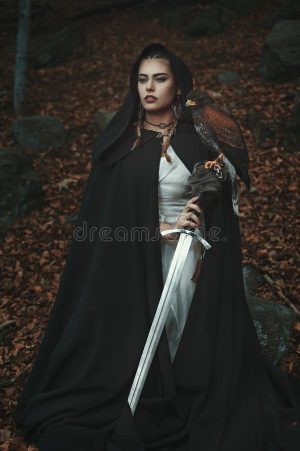 Black hooded woman with sword and hawk. Proud hooded woman with sword and hawk. Forest background royalty free stock images