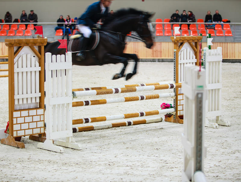 Black horse with rider jumping over obstacle. Riding competition.