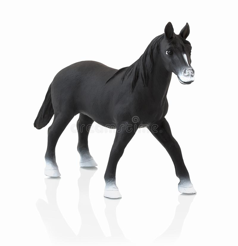 Black horse toy isolated on white background with shadow reflection. Children´s small plastic black horse on white backdrop. Miniature plastic model of royalty free stock photo