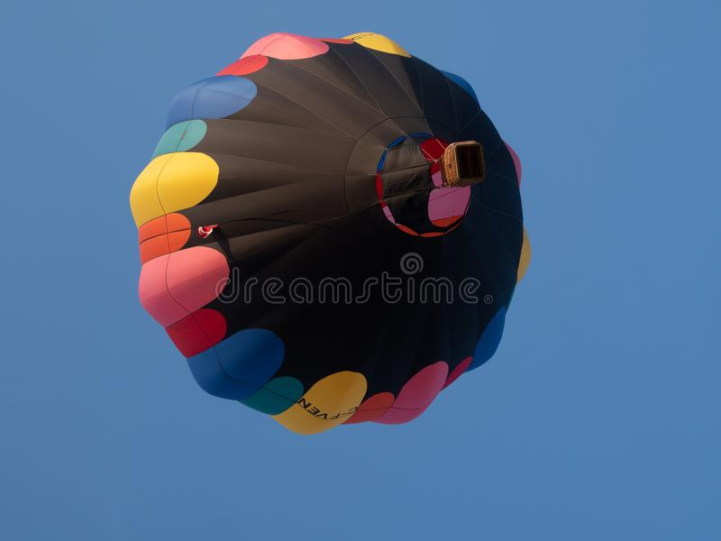 Black Hot Air Balloon with Pink, Red, Orange, Yellow, Blue and G stock images