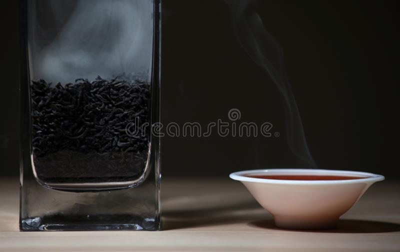 Black Hot Chinese tea cup smoke wooden table dark background nobody royalty free stock photo