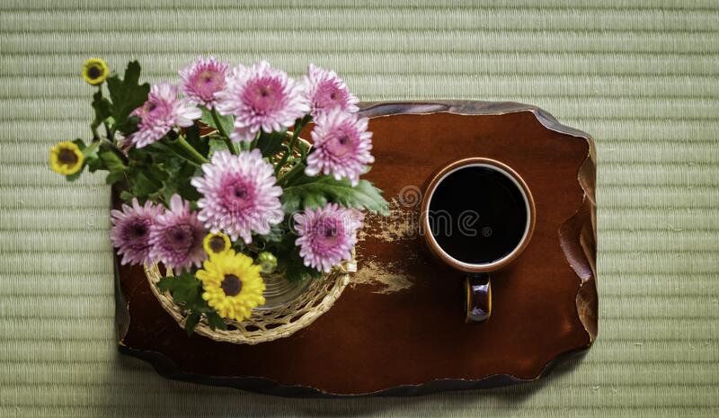 Black hot coffee cup with blurred flower on old brown wooden japanese culture style,dark tone. Black hot coffee cup with blurred flower on old brown wooden, mat stock photo