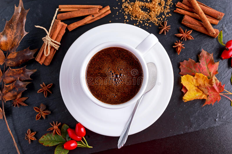 Black hot coffee in white cup with anis stars, brown sugar and cinnamon sticks on stone board autumn theme.  stock images