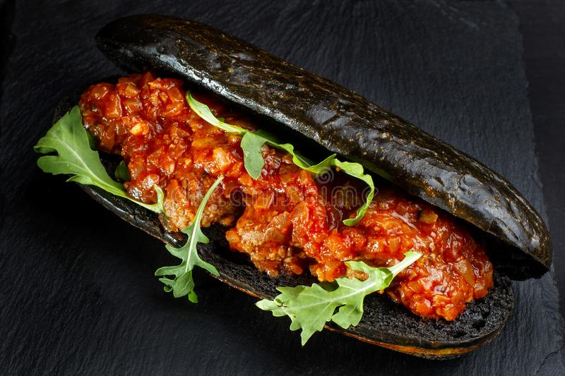 Black hot dog bun with minced meat. Bun tinted ink cuttlefish. Diagonal view stock photography