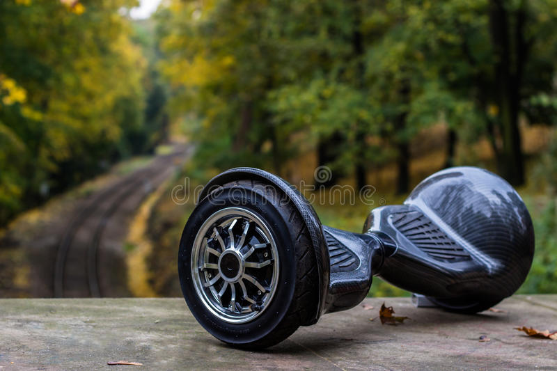 Black hoverboard against the background of railroad rails. A Black hoverboard against the background of railroad rails stock image