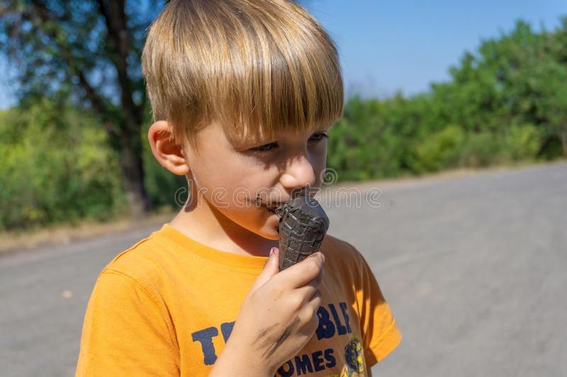 Black ice cream in the hands of a child, the boy eats black ice cream, dirty face and mouth stock images