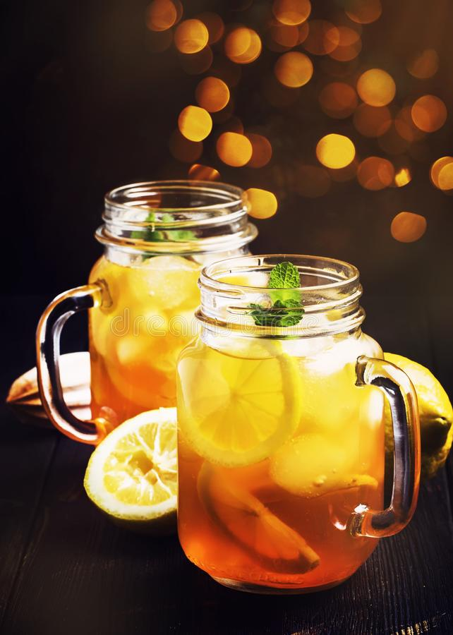 Black ice tea with lemon slice in glass jar on dark kitchen table background, summer cool soft drink, selective focus royalty free stock photos