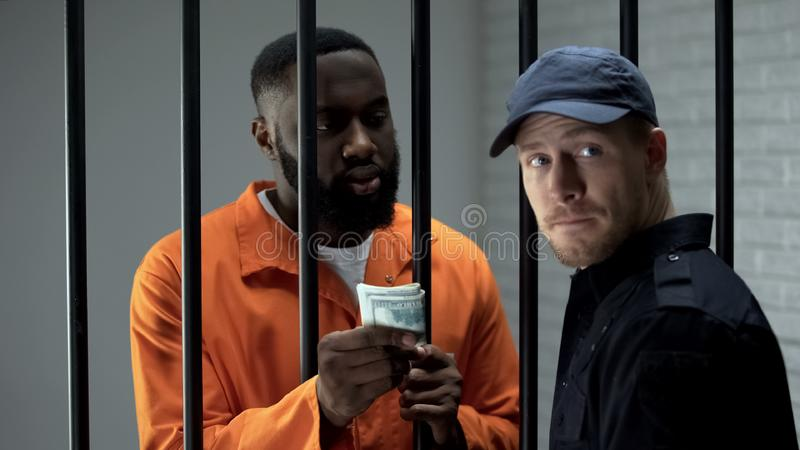 Black imprisoned gangster giving money to prison guard, bribery in jail, cash. Stock photo royalty free stock photography