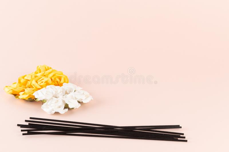Black incense sticks with white and yellow flowers on pink background royalty free stock photo