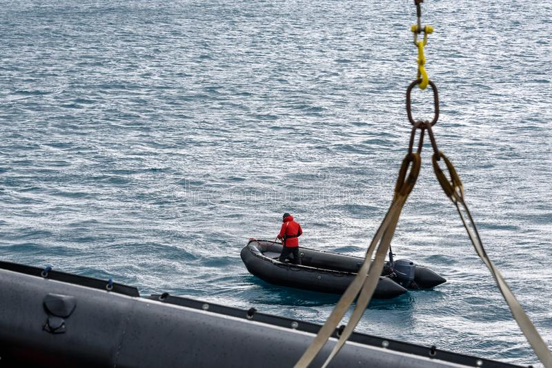Black inflatable boat in water with man in red coat, second boat being winched off ship, Atlantic Ocean royalty free stock images