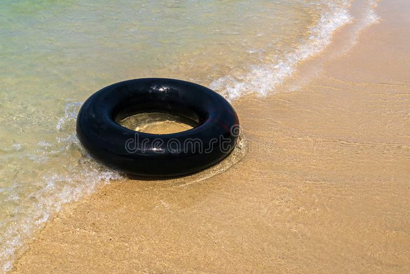 A Black inflatable donut on the seashore. with soft wave of blue ocean in outdoor sun lighting on sandy beach. Background of travel in summer season stock photography