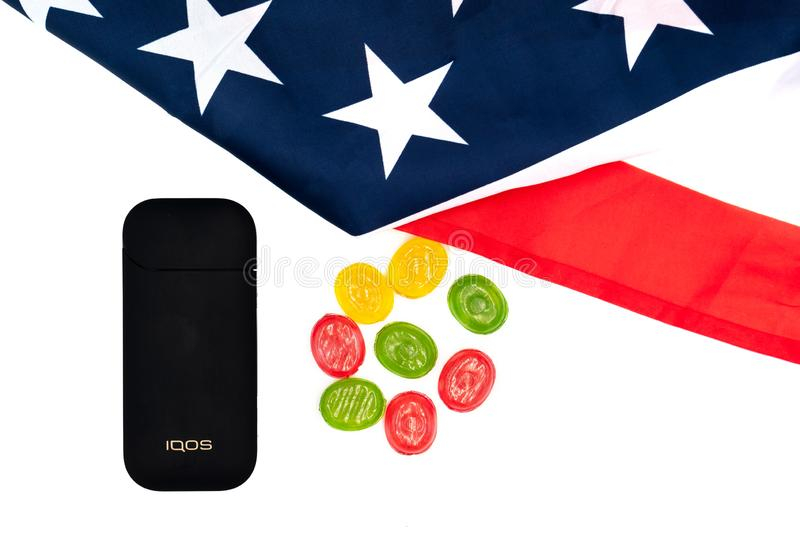 Black IQOS Box, America`s Flag and multicolored sweet candy lollipops on white background. Iqos electronic cigarette ban concept stock photography