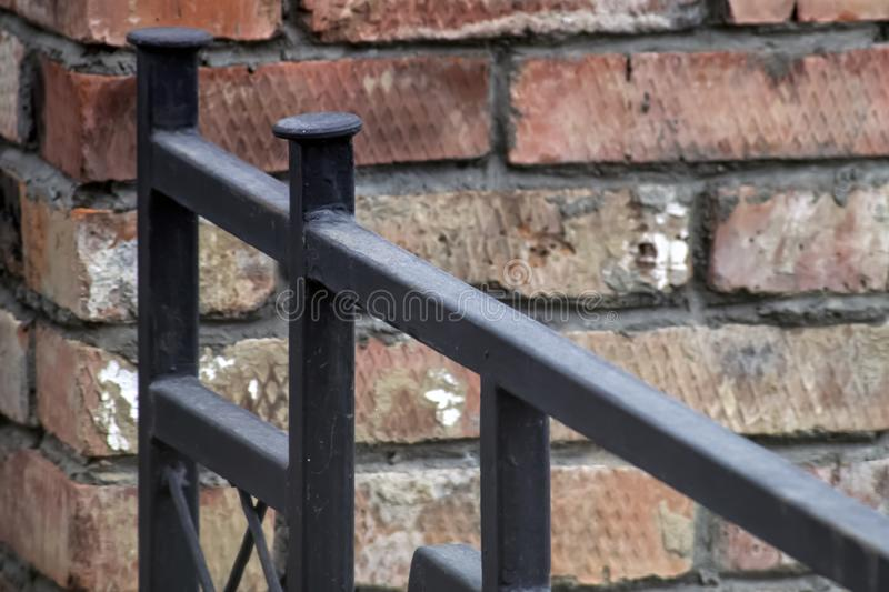 Black iron fence adjacent to the brick wall. Of the building stock images
