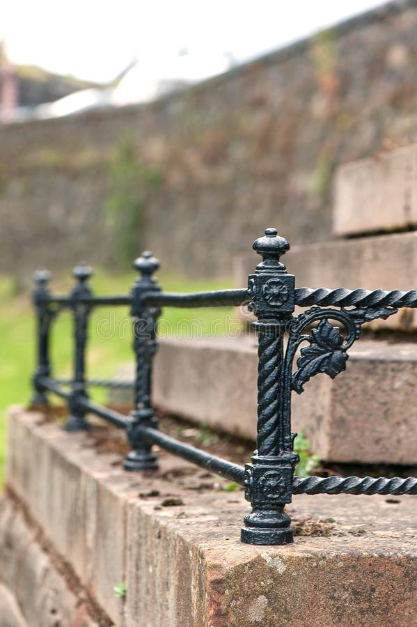 Black iron floral curved fence. Graveyard of Stirling castle. Black iron floral curved fence. Stirling castle graveyard. Summertime outdoors royalty free stock image