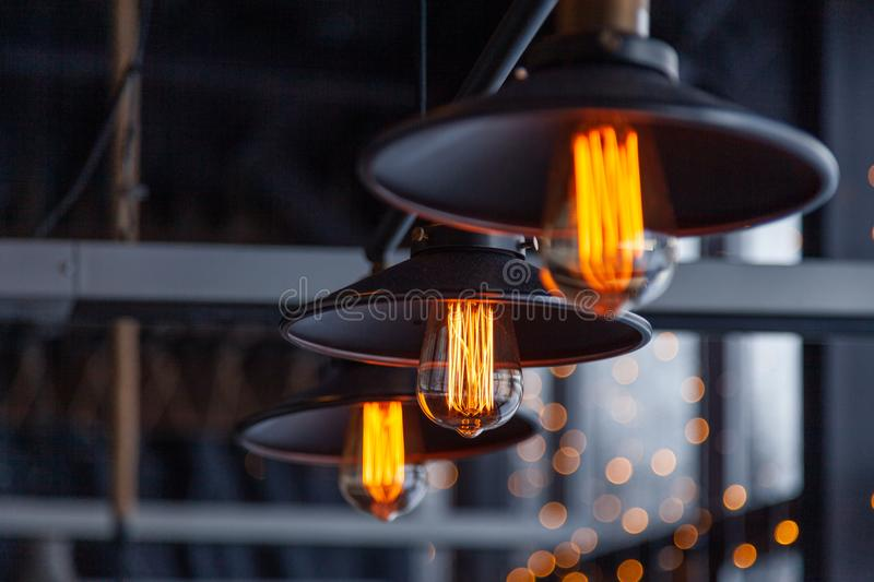 Black iron loft chandeliers with edison lamps on a black background, bokeh. Concept of modern interior design of restaurant, cafe. Black iron loft chandeliers stock image