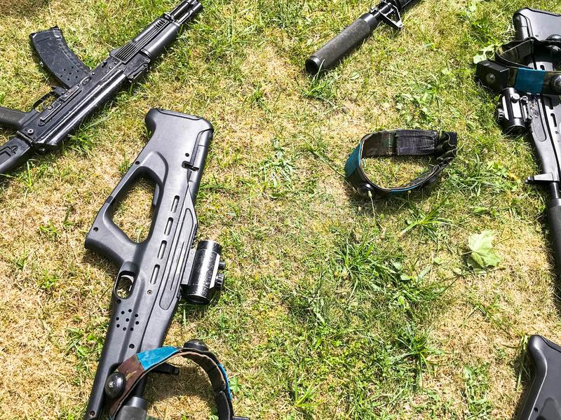 Black iron metal army military machine guns, small arms for soldiers with silencers lie on the background of green grass.  stock photography