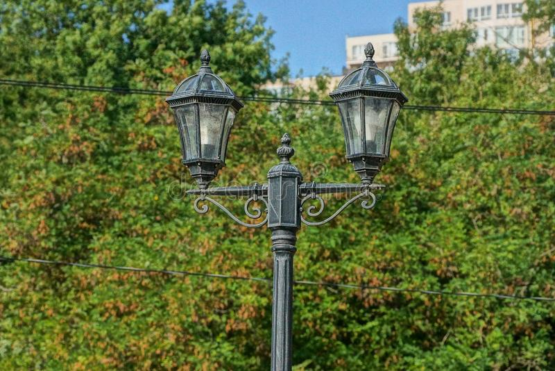 Black iron retro lantern in the park on the background of green leaves and branches stock images