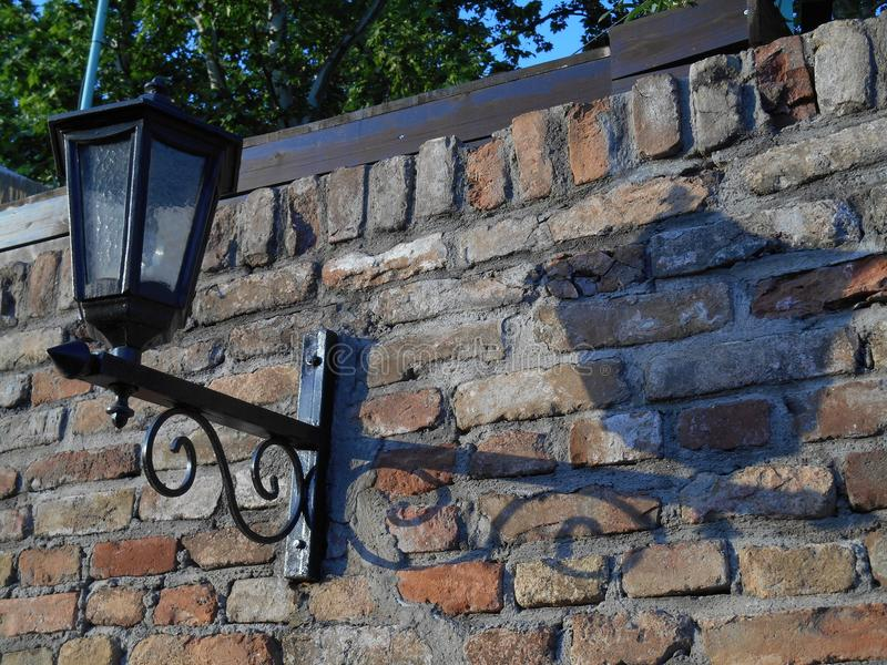 Black iron street lamp with shadow on brickwall stock photography