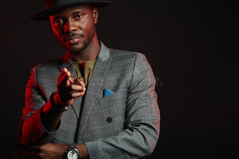 Black jazz musician man wearing fashionable suit and grey hat aiming at camera stock photos