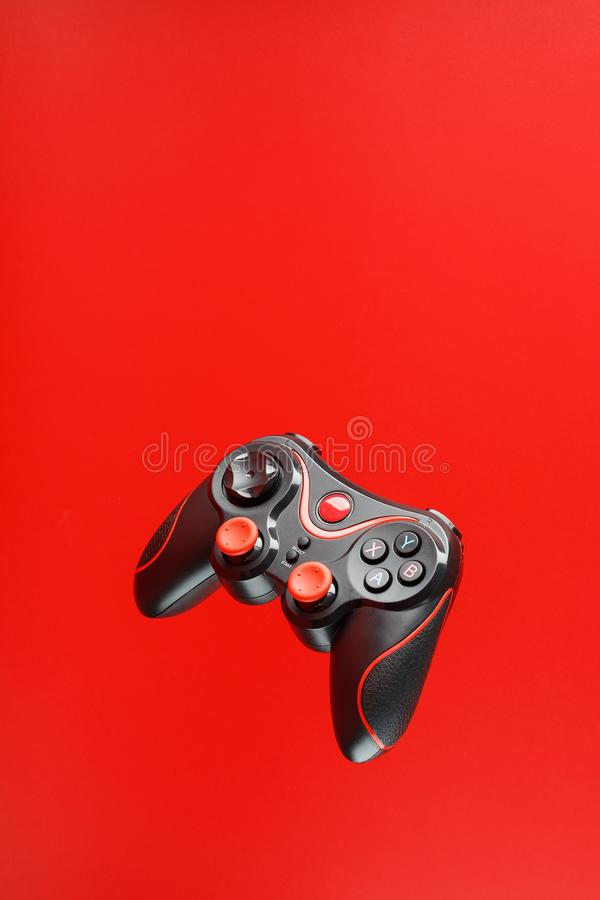 A black joystick game controller hovers isolated on a red background. Interactive entertainment royalty free stock images