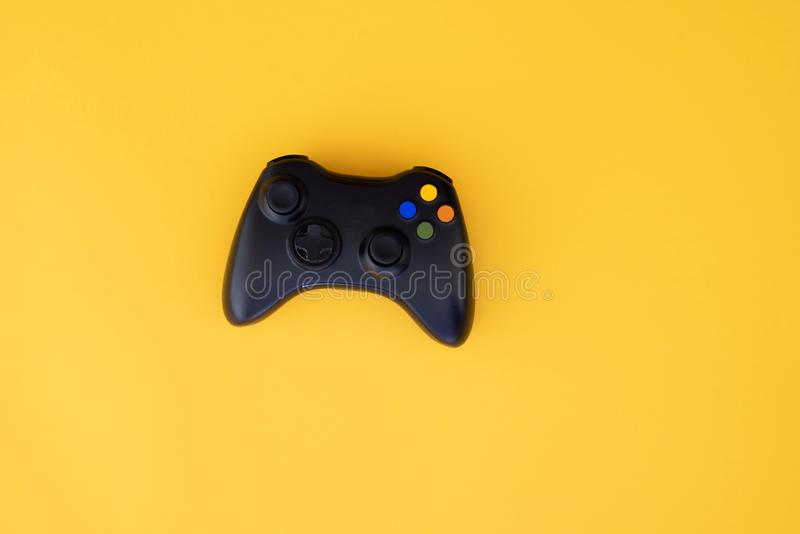 Black joystick is isolated on a yellow background. Video game competition. Gaming concept royalty free stock photos