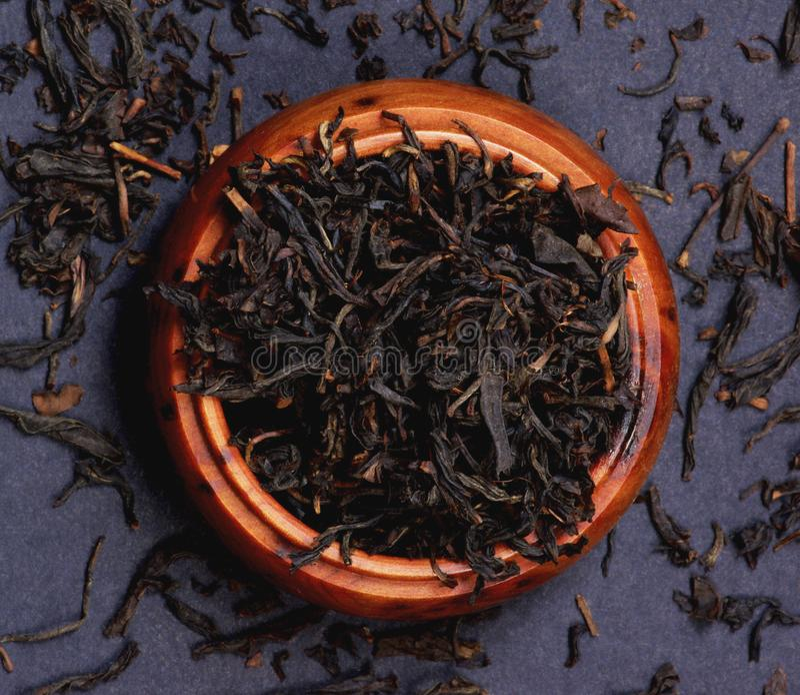 Black Kenya Tea Milima. Arrangement of Black Kenya Tea Milima Leafs in Wooden Jar closeup on Black background. Top View royalty free stock photos